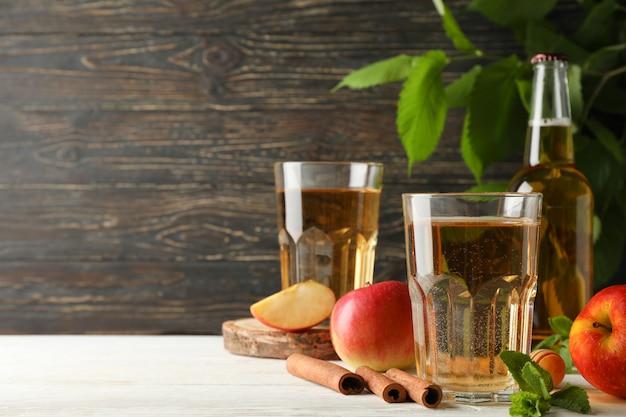 Composição com cidra, canela e maçãs na mesa de madeira Foto Premium
