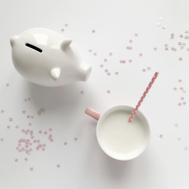 Composição com mealheiro e leite Foto Premium