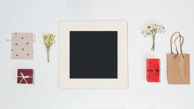 Composição com moldura preta, caixas de presente vermelhas, saco de artesanato, bolsa de lona com formas de coração vermelho e primavera campo de flores sobre fundo branco. maquete plana leiga na moda Foto Premium