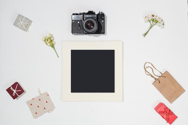 Composição com moldura preta, câmera retro, caixas de presente vermelhas, saco de artesanato, saco de lona com formas de coração vermelho e primavera campo de flores sobre fundo branco. maquete plana leiga na moda Foto Premium