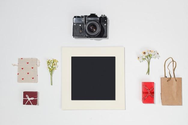 Composição com moldura preta, câmera retro, caixas de presente vermelhas, saco de artesanato, saco de lona com formas de coração vermelho e primavera campo de flores sobre fundo branco. Foto Premium