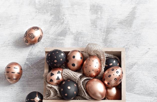 Composição com ovos de páscoa pintados nas cores dourado e preto com enfeites Foto gratuita