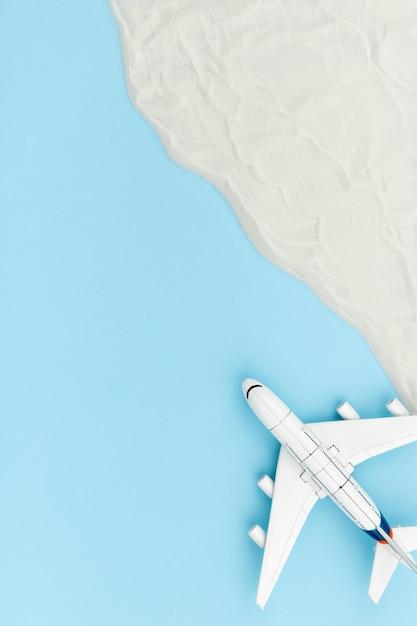 Composição criativa com avião de brinquedo e areia. conceito de viagens de férias Foto Premium