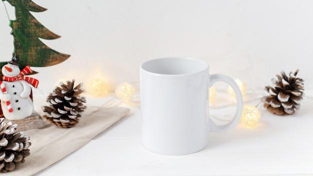 Composição da mesa de natal. xícara de chá, cones de abeto e decoração. parede branca Foto gratuita
