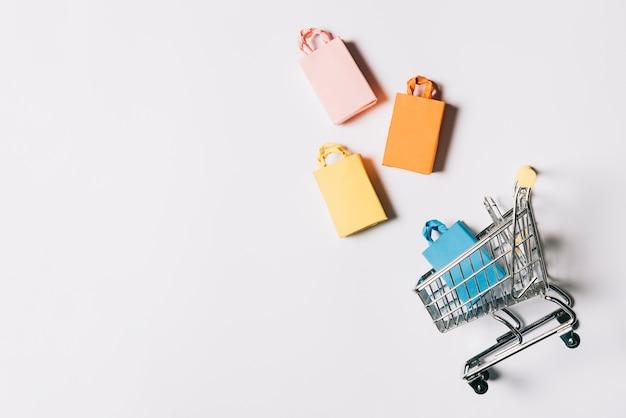 Composição da sexta-feira negra com quatro sacos e carrinho Foto gratuita