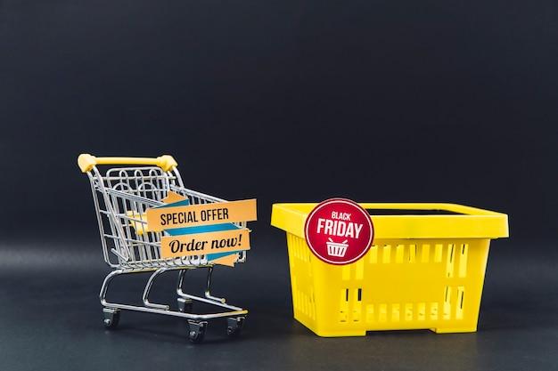 Composição das vendas na sexta feira preta com carrinho e cesta Foto gratuita