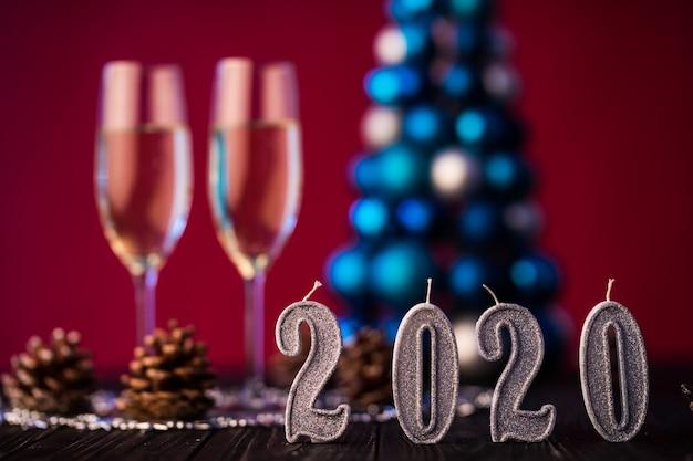 Composição de ano novo 2020 com champanhe e espaço para texto contra árvore e luzes de natal borradas. conceito de ano novo e natal Foto gratuita