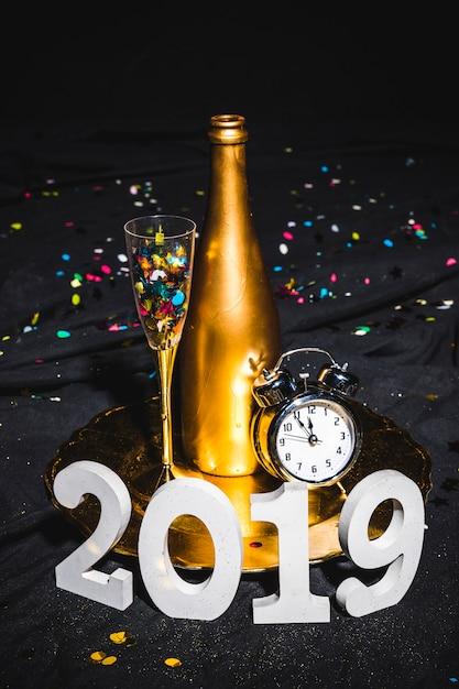Composição de ano novo de champanhe e relógio Foto gratuita
