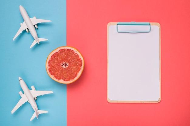 Composição de aviões grapefruit e quadro de esboço branco Foto gratuita