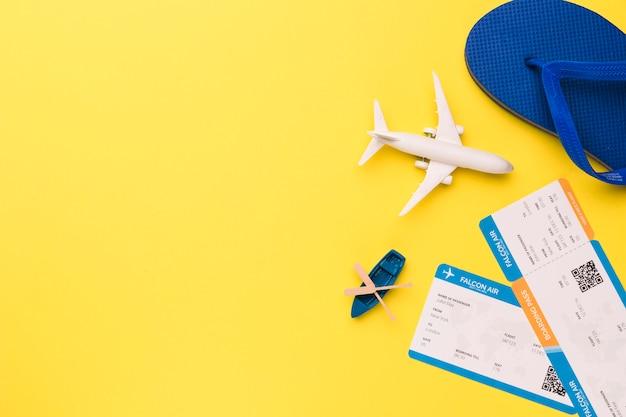 Composição de bilhetes de barco de avião de brinquedo e flip-flops Foto gratuita