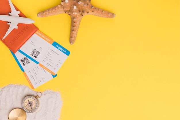 Composição de bilhetes de passaporte pequeno avião estrela e bússola na toalha Foto gratuita