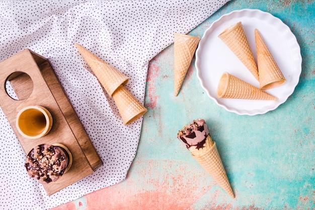 Composição de copos de bolacha vazia e sorvete em cones de waffle Foto gratuita
