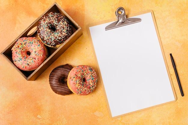 Composição de donut plana leigos com prancheta Foto gratuita