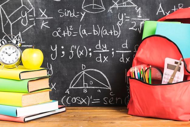 Composição de escola com livros e mochila na mesa Foto gratuita
