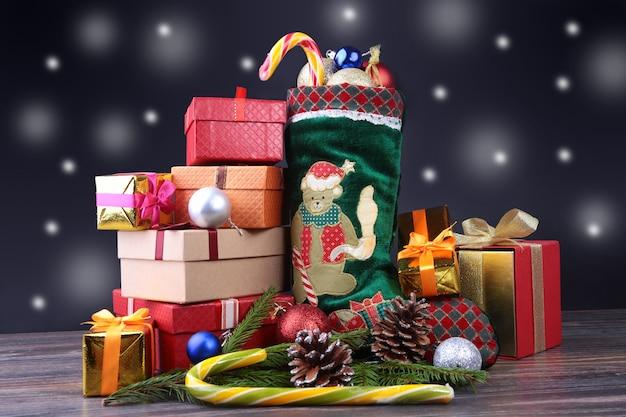Composição de feliz natal. sapato do papai noel com caixas de presente em penas onduladas com neve e flocos de neve. Foto Premium