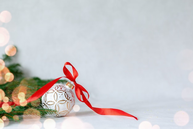 Composição de férias de natal com bola branca e fita vermelha em fundo claro Foto Premium