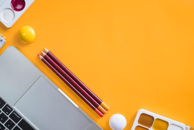 Composição de ferramentas de laptop e papelaria para pintura Foto gratuita