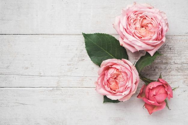 Composição de flores de botões de rosa e folhas cor de rosa em uma superfície de madeira branca. Foto Premium