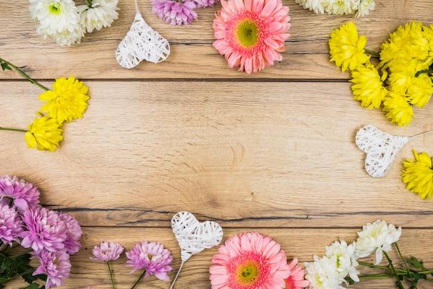Composição de flores frescas perto de corações ornamentais em varinhas Foto gratuita