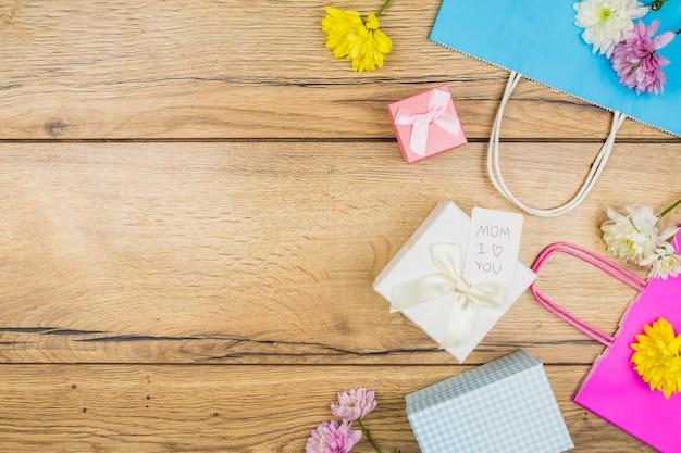 Composição de flores frescas perto de tag em caixas de presentes perto de pacotes de papel Foto gratuita