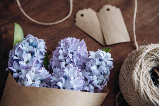 Composição de flores. jacintos de buquê em uma mesa de madeira. dia dos namorados. vista plana leiga, superior. Foto Premium