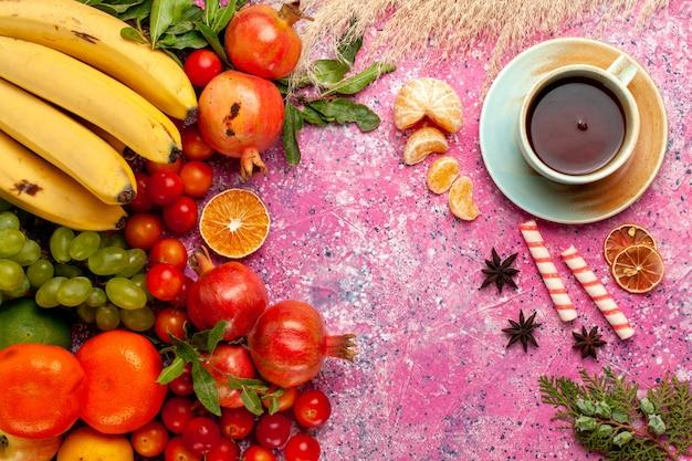 Composição de frutas frescas de vista frontal com uma xícara de chá na mesa rosa claro Foto gratuita