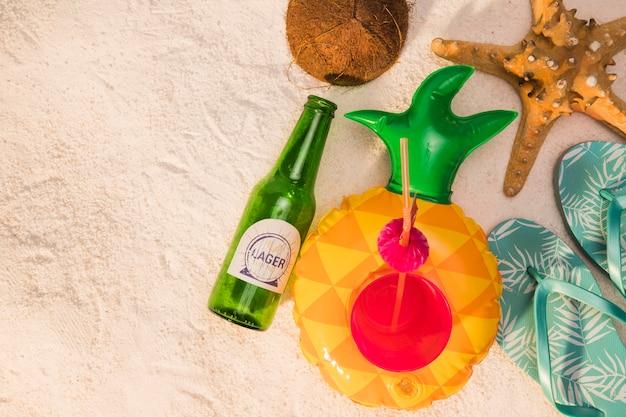 Composição, de, garrafa, coquetel, sandálias, starfish, coco, ligado, areia Foto gratuita