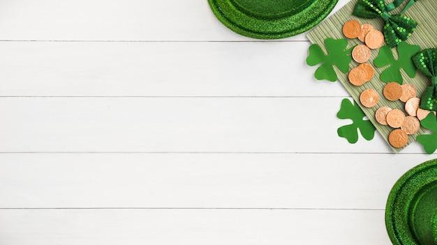 Composição de laços perto de chapéus, moedas e trevos de papel verde a bordo Foto gratuita
