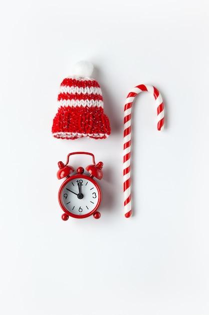 Composição de natal, bala de cana, pequeno relógio analógico, chapéu listrado na parede branca. estilo mínimo. vista do topo. festivo, conceito de férias. Foto Premium
