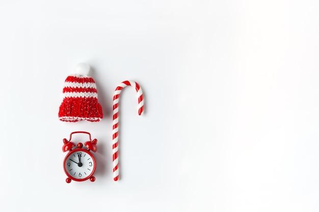 Composição de natal, bala de cana, pequeno relógio analógico Foto Premium