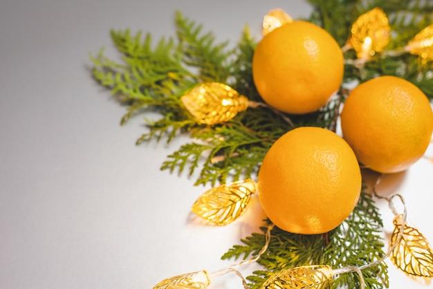 Composição de natal com frutas laranja, ramo de planta e guirlanda em fundo cinza Foto Premium