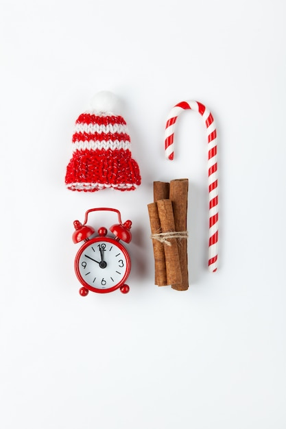 Composição de natal com pirulito, pequeno relógio analógico, chapéu listrado e paus de canela Foto Premium