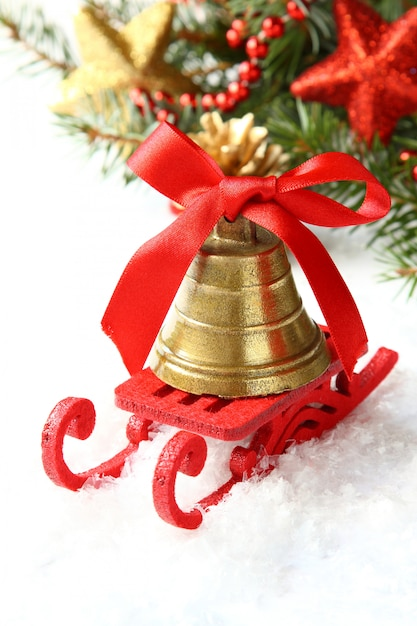 Composição de natal com trenó e sino de ouro sobre branco Foto Premium