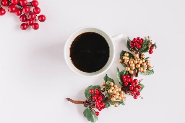 Composição de natal de café com bagas vermelhas Foto gratuita
