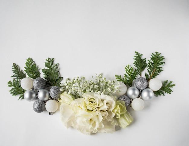 Composição de natal de flores brancas frescas, bolas de natal prateadas e thuja Foto Premium