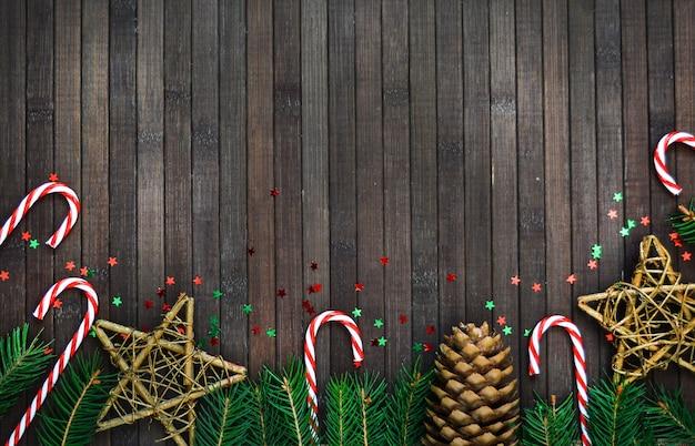 Composição de natal de um galho de árvore, chapéu de papai noel, estrelas de doces, pinha, no padrão de férias de ano novo de madeira. copyspace. Foto Premium