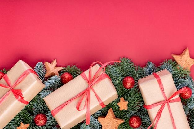 Composição de natal. decorações de natal vermelho, galhos de árvore do abeto com caixas de presente de brinquedos em fundo vermelho. vista plana, vista superior, cópia espaço Foto Premium