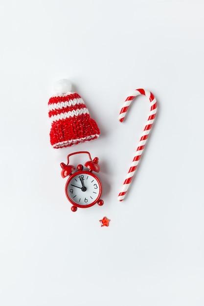 Composição de natal, doces de cana, pequeno relógio analógico, chapéu listrado, estrela, dispostos em forma de coração em background.media branco, cartão de felicitações. Foto Premium