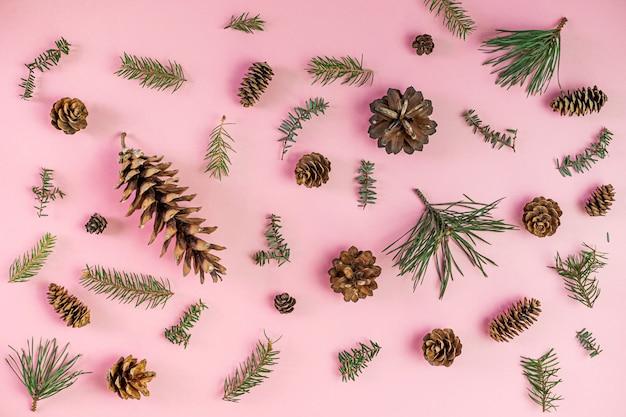 Composição de natal. galhos de árvores coníferas e cone de fogo na rosa. natal, inverno. vista plana, vista superior Foto Premium
