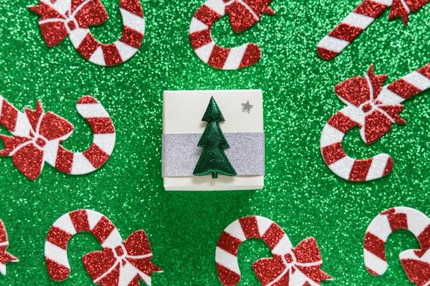 Composição de natal. padrão de bastão de doces de natal e caixa de presente em fundo verde brilhante. boas festas e conceito de ano novo. Foto Premium