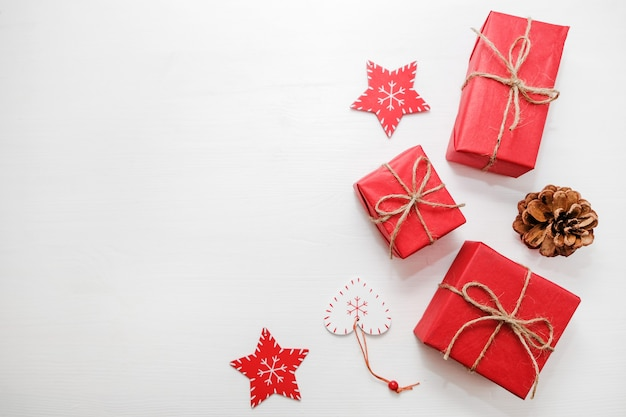 Composição de natal. presentes, cones de abeto, decorações vermelhas sobre fundo branco. Foto Premium