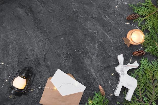 Composição de natal. presentes, envelope, galhos de árvore do abeto, decorações brancas sobre fundo preto. natal, inverno, ano novo conceito. vista plana, vista superior, cópia espaço Foto Premium