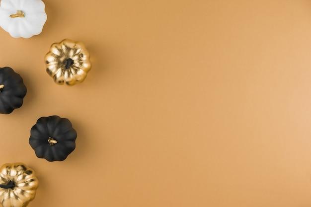 Composição de outono com abóboras decorativas douradas, brancas e pretas Foto Premium