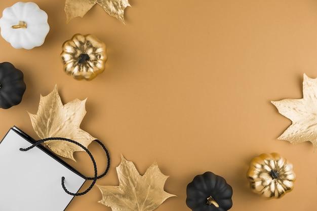 Composição de outono com folhas de bordo douradas, abóboras decorativas e sacola de compras Foto Premium