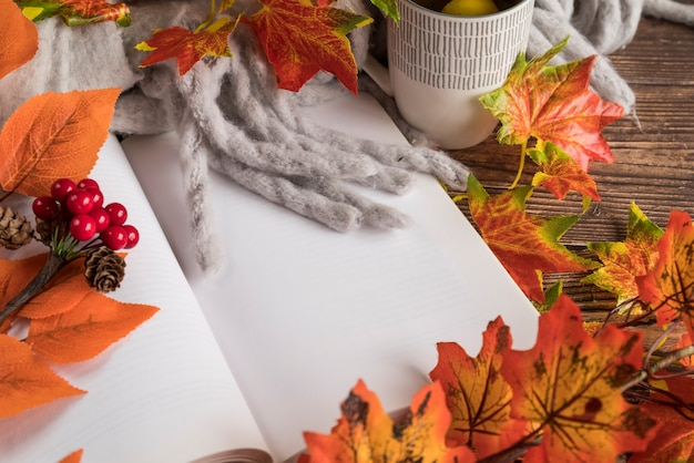 Composição de outono com o livro aberto na mesa Foto gratuita