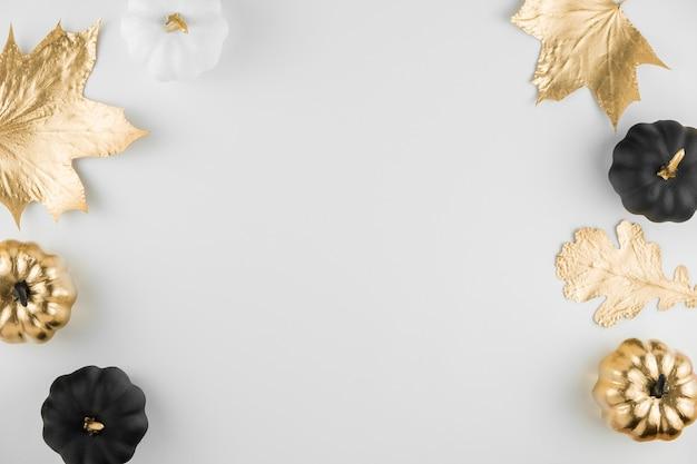 Composição de outono. moldura feita de folhas douradas de outono e abóboras decorativas Foto Premium