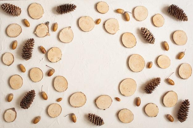Composição de outono, moldura feita de pinhas, bolotas e pequenos tocos de madeira. Foto Premium