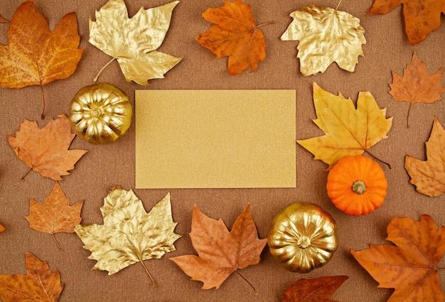 Composição de outono plana leiga com folhas amarelas e douradas de outono e abóboras Foto Premium