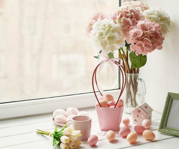 Composição de páscoa com hortênsias rosa e brancas em vaso, tulipas amarelas e ovos cor de rosa Foto Premium