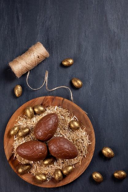 Composição de páscoa com ovos de chocolate na cor de fundo de madeira Foto Premium